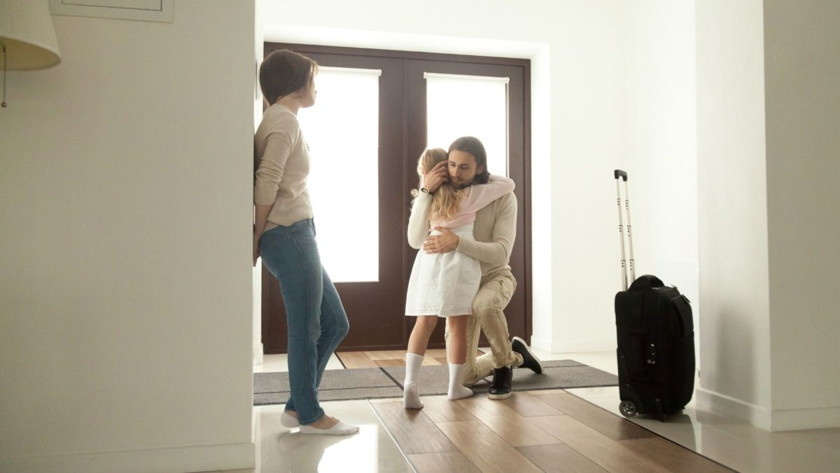Child hugging a parent who is leaving with a suitcase