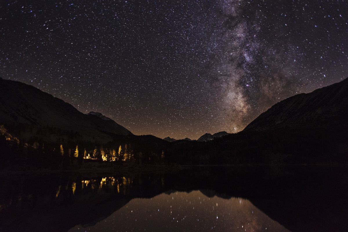 Night Sky reflected in a lake surrounded by mountains and a cabin