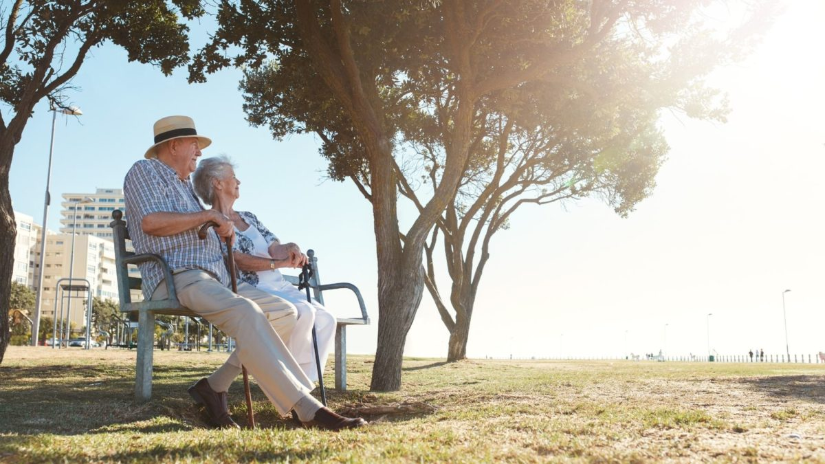 Elderly couple sitting together on a park bench on a sunny day