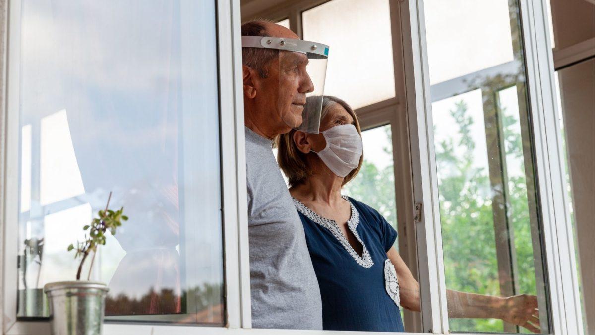 Elderly couple looking out a window wearing PPE
