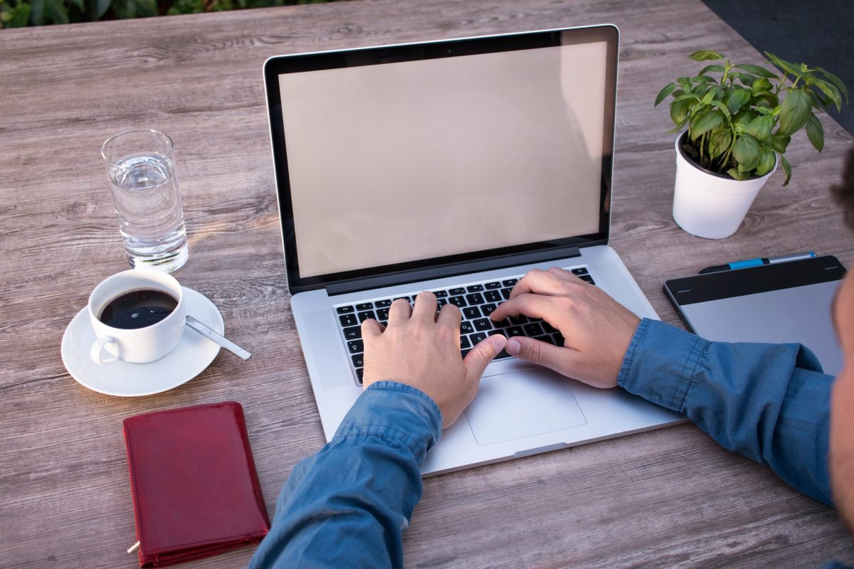 person typing on a laptop with coffee