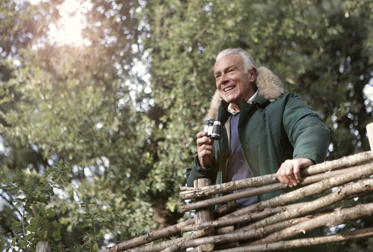 senior man using binoculars in a forest
