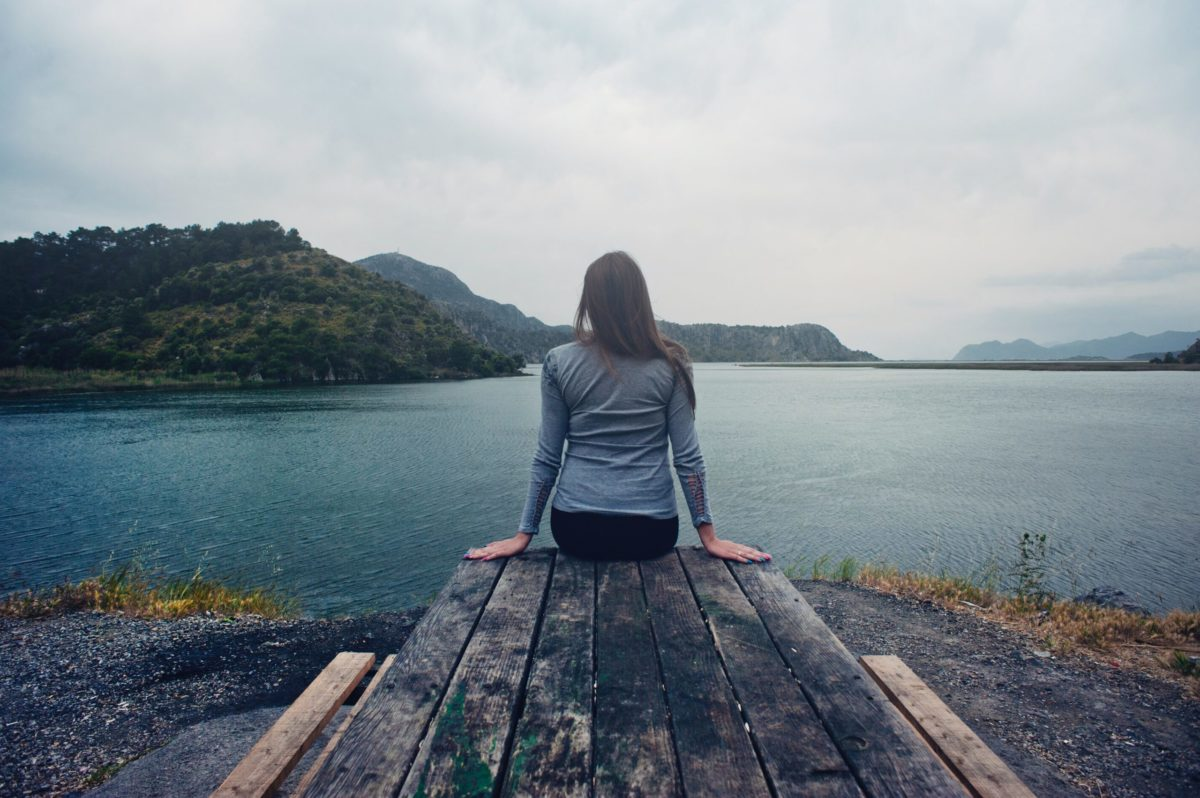 woman sitting on a dock look out into a lake with mountains