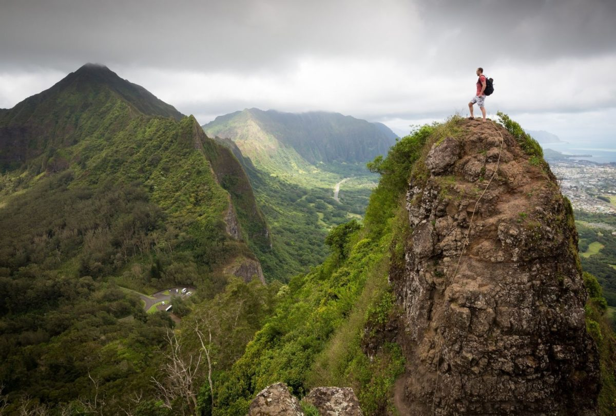 man standing on a mountain top looking at the scenery